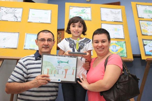 Aluna Manuela com seu troféu, desenho e seus pais   Sd Tiago Lopes