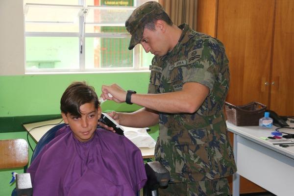 Militar da BAFL cortando cabelo de criança da comunidade