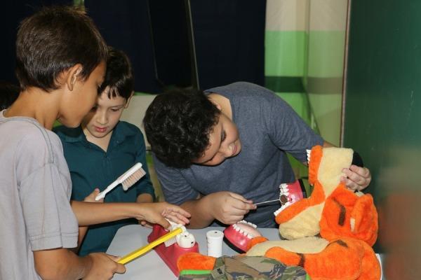 Crianças praticando como deve ser feita a escovação dos dentes