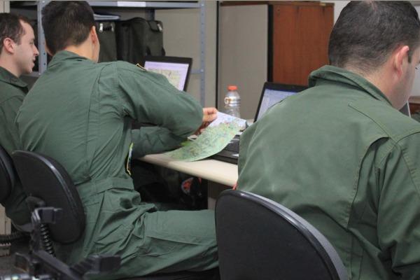 Pilotos realizando planejamento para a missão