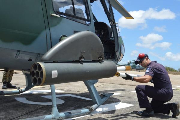 Militar prepara armamento no helicóptero