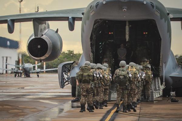 Soldados embarcam no avião para um dos testes